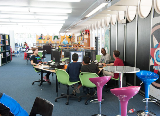 people using the computer area of the library