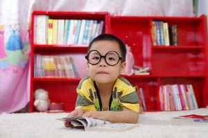 child in black o-shaped glasses reading a book