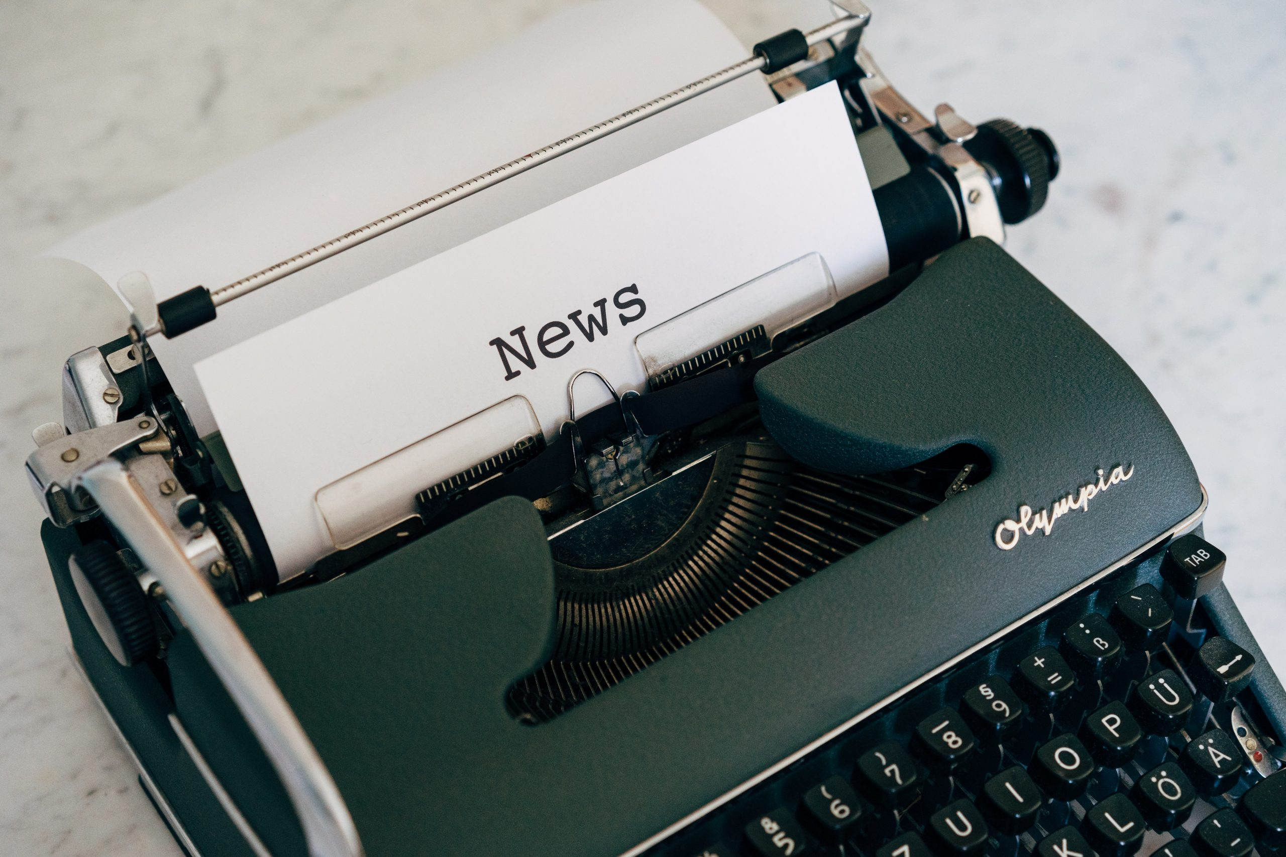typewriter with paper headline of news